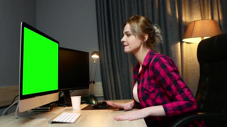 készítő : Woman  works on her computer, works in office. Monitor green screen, side view.