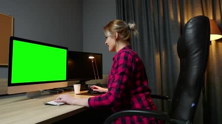 creator : Woman  works on her computer, works in office. Monitor green screen, side view.