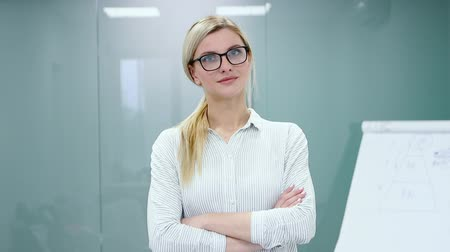 Young blonde businesswoman in office clothes and glasses is looking at camera and smiling.