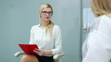 Human resource specialist young woman in glasses is talking with applicant woman at job interview.