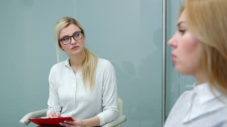 psychotherapist : Psychologist is attentively listening client woman talking about her problems at therapy.