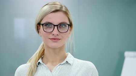 espetáculos : Young blonde businesswoman in office clothes and glasses is looking at camera and smiling.