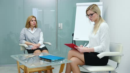 magyarázza : Woman psychologist explains to the patient plan for the upcoming therapy. First therapy session. Stock mozgókép