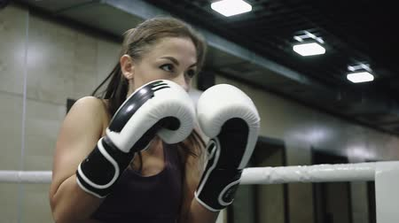 Woman is doing kickboxing training to practicing hand punches in gloves in gym.