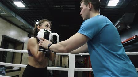 kickbox : Trainer is explaining the punch technique to the woman boxer on ringside.