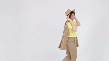 blúz : Young woman in yellow blouse, beige hat and scarf is posing at camera on light background.