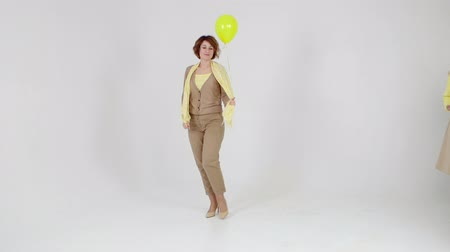 Defile of young woman with yellow balloon in hand is walking in trousers and blouse on light background.