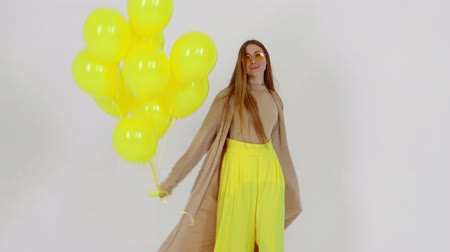 Girl in yellow skirt with yellow balloons in hands is posing at the camera at light background.
