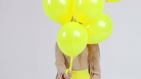 двадцатые годы : Girl in yellow skirt with yellow balloons in hands is posing at the camera at light background.