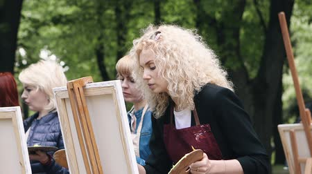 passatempos : Poltava, Ukraine - may 2019: A group of women of different ages are learning to draw pictures in the park