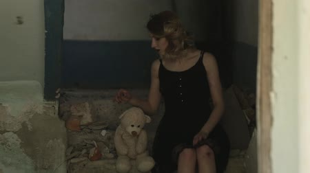 unloved : Girl sits in a destroyed room and playing with toy