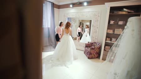 подвенечное платье : Female trying on wedding dress in a shop with women assistant.