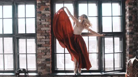 fishnet tights : Ballet dancer in a bright red skirt on the background of the window Stock Footage