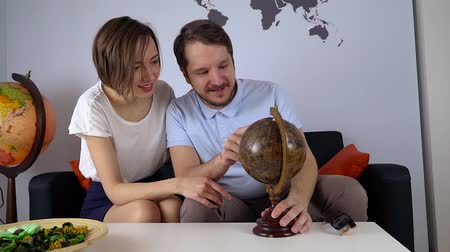 решить : Young couple look the world map to decide the next trip