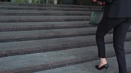 идущий : Lower part of business woman in formal suit walking up the outdoor stair.
