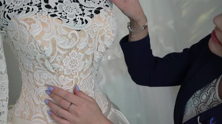 подвенечное платье : Woman choosing wedding dress in shop