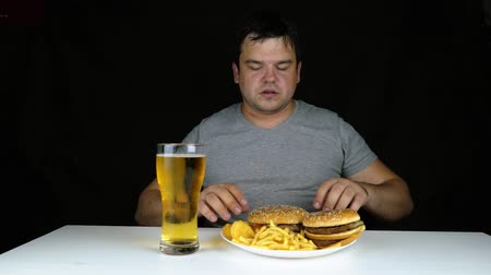healthyfood : Diet failure of fat man eating fast food hamberger. Happy smile overweight person who spoiled healthy food by eating huge hamburger on fork. Junk meal leads to obesity. Refusal from harmful food. Stock Footage