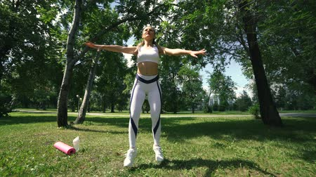 tilts : Woman doing fitness exercises outdoor. Female runner stretching before running marathon in green forest. Slim girl in sports clothes doing stretching exercises in park. Outdoor workout