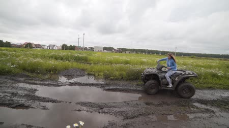 quadbike : Beautiful woman rides on a quad bike along a rural road, mud is flying under the wheels, splashes Stock Footage