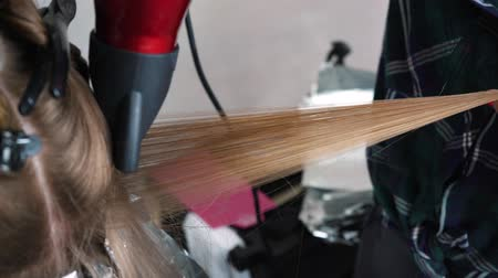 latino americana : Blowing hair when staining. Drying long brown hair with a hair dryer and a round brush. Close-up.