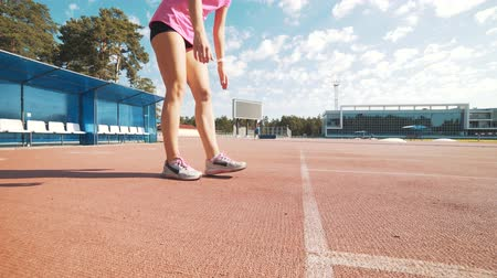 five striped : Track runner woman putting her hands at starting line