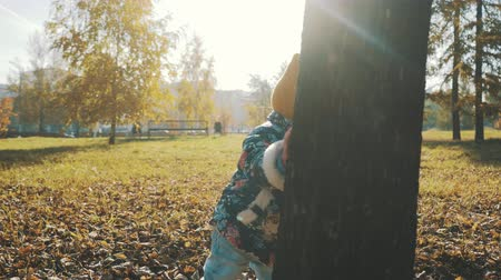 ищу : little girl hiding behind a tree in the autumn forest