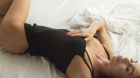 Sensual young women wearing black lingerie in bed