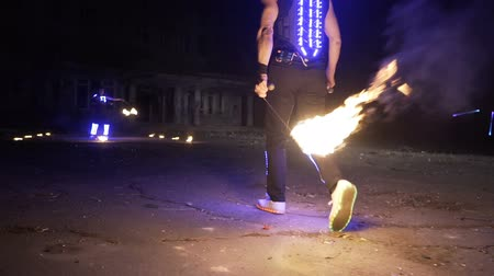 fire show, dancing with flame, a man in a suit LED dances with fire, draws a fiery figure in the dark