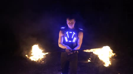 Fire show performance. Handsome male fire juggler performing contact manipulation with fire baton with several wicks Wideo
