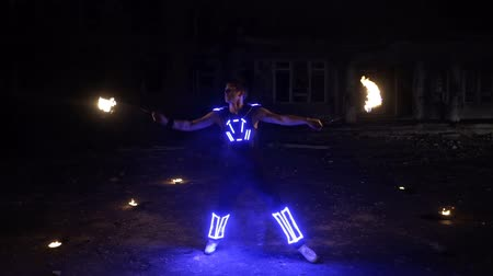 movimentar se : Boy shows different tricks with burning pois rotation at evening fire show.
