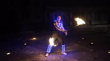 performer : Fire show. Handsome male fire performer twirling fire baton with several wicks. Stock Footage