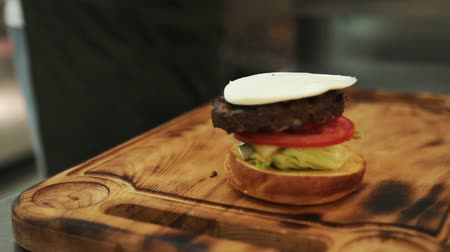 bacon burger : Close up view of assembling a beef hamburger lunch with fresh lettuce being placed on sesame bread bun then topped with freshly cooked beef patty. Stock Footage