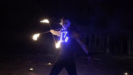 затянуть : Fire show performance. Handsome male fire performer twirling and tossing up fire baton staff ignited from both sides.