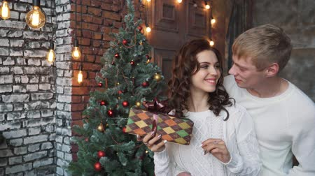 A young man in a white sweater gives a gift to his girlfriend. Happy New year, merry Christmas