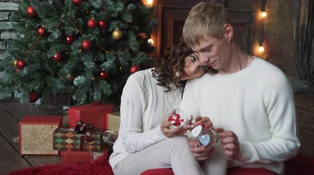 x mas : young couple, man and woman, smiling, happy, wearing Christmas decoration, holding new years toys. Stock Footage