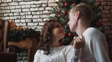 A young handsome husband hugging his wife if front of a new year tree, presents and tangerines around them. A family christmas celebration together surrounded by presents, tangerines. Стоковые видеозаписи