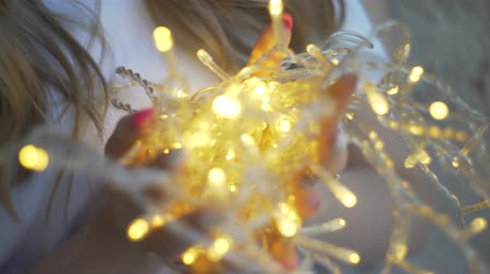 tilts : Beautiful young girl against the wall, the girl holding a garland, Christmas lights. Stock Footage