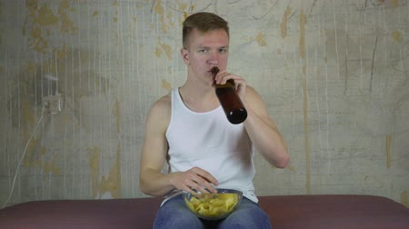 league : a young guy with a bottle of beer and chips watching TV