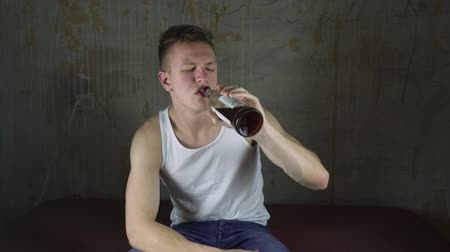 виски : Young man is sad. He is drinking alcohol. Drowning sorrow in alcohol. Drinking whiskey. Drinking brandy. Drinking rum. Cure for heartache Стоковые видеозаписи