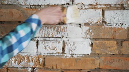 püskül : Red brick paint in white. In the hands of girls paint brush. The girl makes repairs. Stok Video
