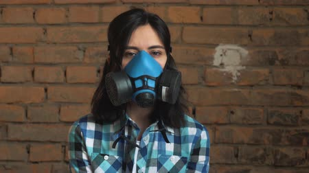 respirator : The woman wearing the mask of air pollution from traffic, on a brick background . Shes looking at the camera. Shallow depth of field. Stock Footage