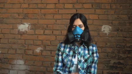 emissions : The girl takes off the mask from air pollution. On brick wall background, respiratory mask.