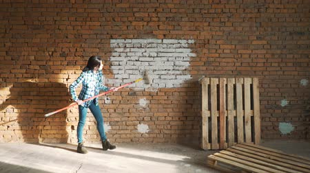 ремонт : Girl Builder, with dark hair, paint roller brick wall.