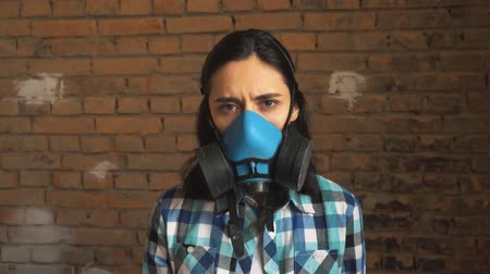 estuque : Girl in the respirator smiling in unfinished apartments, against a brick wall Vídeos