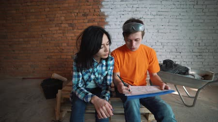 инспектор : The customer sends the plan of the house to the Builder, explains how to redevelop the house. A man and a woman are watching their house plan.