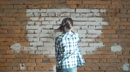 renovar : Beautiful young woman doing wall painting. Stock Footage