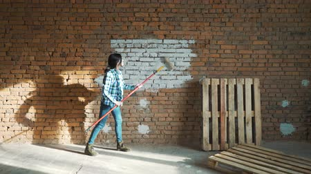 lakásfelújítás : A young girl paints a brick wall in her house with a roller. Painting walls with a roller. Paint the bare walls with a roller of white paint. Stock mozgókép