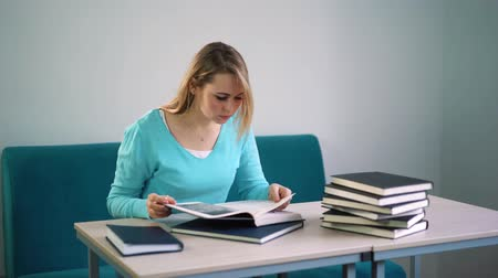 hafifletmek : woman in blue jacket reading a book in the library Stok Video