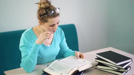 lehkost : woman in blue jacket reading a book in the library Dostupné videozáznamy