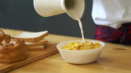 oat flakes : Milk pouring into cereal bowl in slow motion